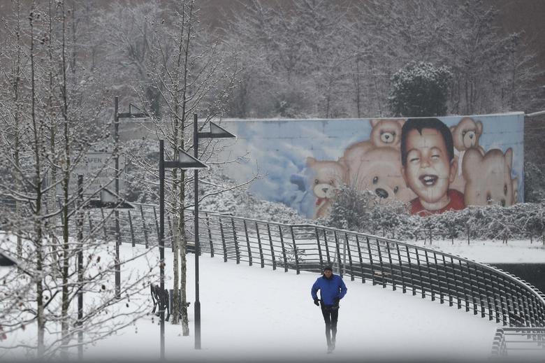 A person runs past a graffiti depicting the drowned Syrian toddler Aylan Kurdi in Frankfurt, Germany, January 10, 2017. REUTERS/Kai Pfaffenbach