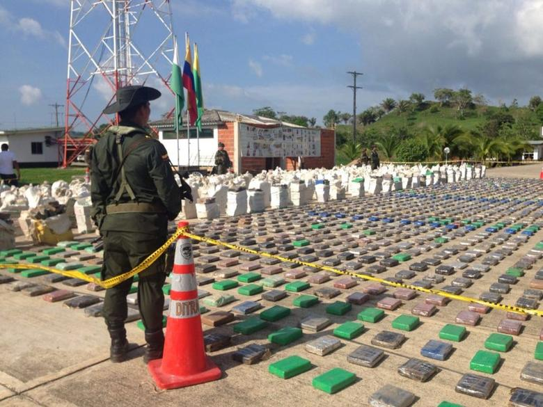 A Colombian national policeman stands guard in front of packages of cocaine, which were confiscated in Turbo province near the border with Panama, May 15, 2016.   Colombian  Police/Handout via REUTERS