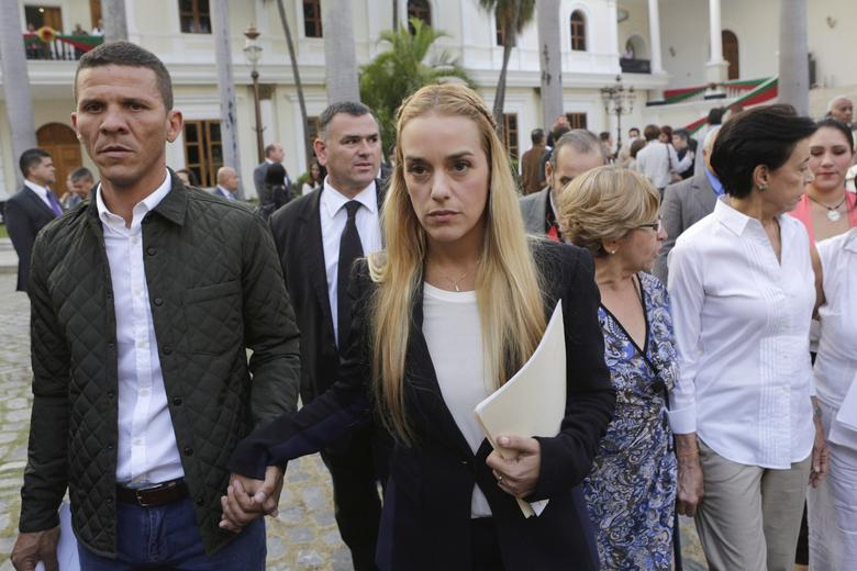 Lilian Tintori (C), wife of jailed opposition leader Leopoldo Lopez, holds hands with opposition deputy Gilbert Caro (L) as she leaves after a meeting with deputies of the Venezuelan coalition of opposition parties (MUD) and relatives of imprisoned dissidents at the National Assembly in Caracas, January 11, 2016. REUTERS/Marco Bello/File Photo