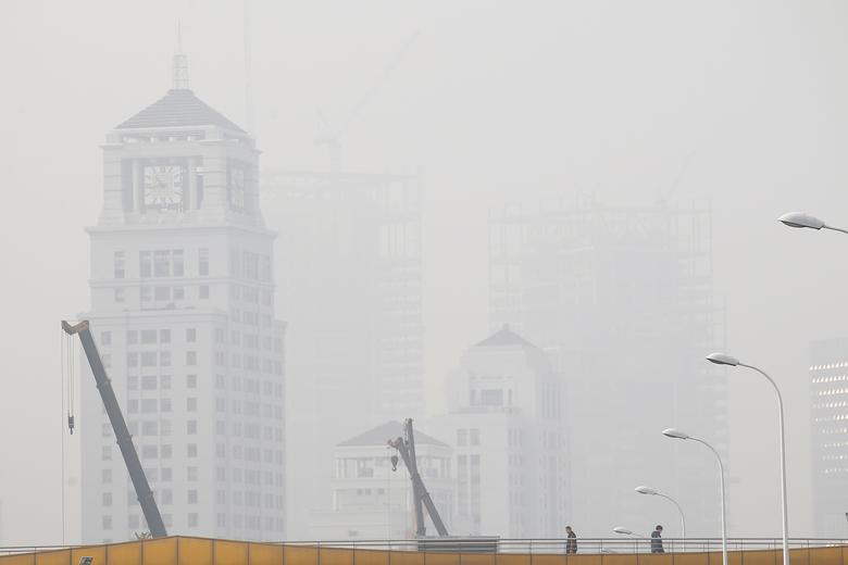 People walk on a bridge amid heavy smog in Shanghai, China December 23, 2016.  REUTERS/Aly Song
