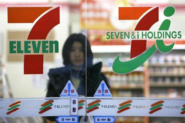 A woman walks behind the logos of Seven & I Holdings Co. (R) and 7-Eleven at a store in Tokyo January 14, 2009.   REUTERS/Stringer (JAPAN BUSINESS) - RTR27BC2