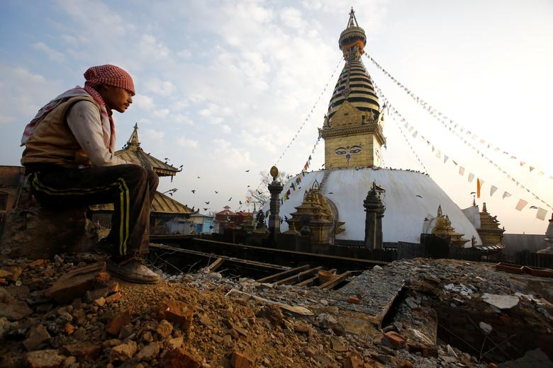 A laborer sits on top of the debris of a monastery damaged during the 2015 earthquake, in Swayambhunath Stupa, a UNESCO world heritage site in Kathmandu, Nepal January 11, 2017. REUTERS/Navesh Chitrakar