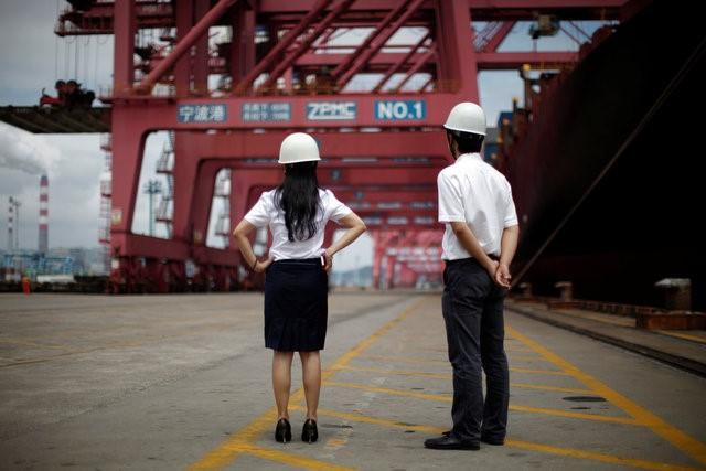 Employees stand next to a container ship at Ningbo port in Ningbo, Zhejiang province June 21, 2012. REUTERS/Carlos Barria/File Photo