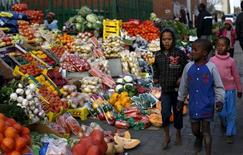 Children walk past a vegetable stall in Soweto July 23, 2015.   REUTERS/Siphiwe Sibeko