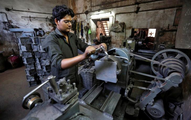 A worker operates a lathe inside a small scale manufacturing unit in Ahmedabad, India, April 12, 2016.  REUTERS/Amit Dave/Files
