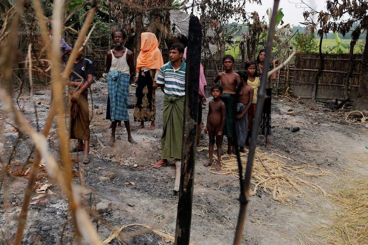 A family stands beside remains of a market, which was set on fire in Rohingya village, outside Maungdaw in Rakhine state, Myanmar October 27, 2016. REUTERS/Soe Zeya Tun