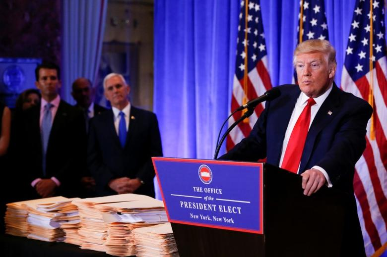 Donald Trump Jr. (L) and Vice President-elect Mike Pence are seen in the background as U.S. President-elect Donald Trump gives a press conference in Trump Tower, Manhattan, New York, U.S., January 11, 2017. REUTERS/Shannon Stapleton