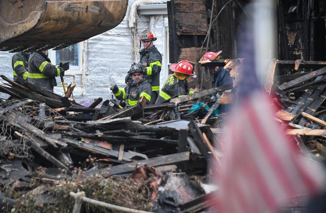 Firefighters sift through debris at the scene of an overnight house fire, where several children were presumed dead and others including the mother injured, in Baltimore, Maryland, U.S., January 12, 2017.  REUTERS/Bryan Woolston