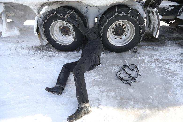 Semi-truck driver Don Kerns removes chains from his truck during record rain and snow outside Lakeview, Oregon, U.S., January 5, 2017.  REUTERS/Jim Urquhart