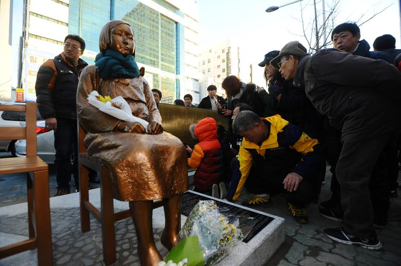 A flower is laid on a statue of a girl that represents the sexual victims by the Japanese military during a rally in front of Japanese Consulate in Busan, South Korea, December 30, 2016.   Yeo Joo-yeon/News1 via REUTERS