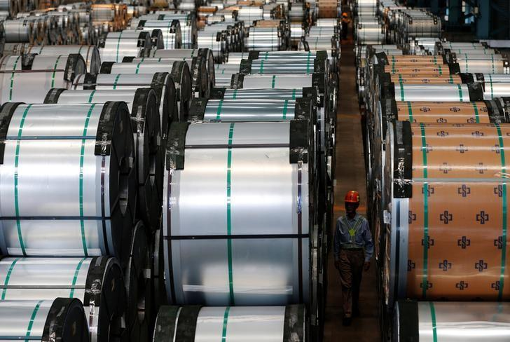 A worker walks past rolls of steel inside the China Steel Corporation factory, in Kaohsiung, southern Taiwan August 26, 2016. REUTERS/Tyrone Siu/Files