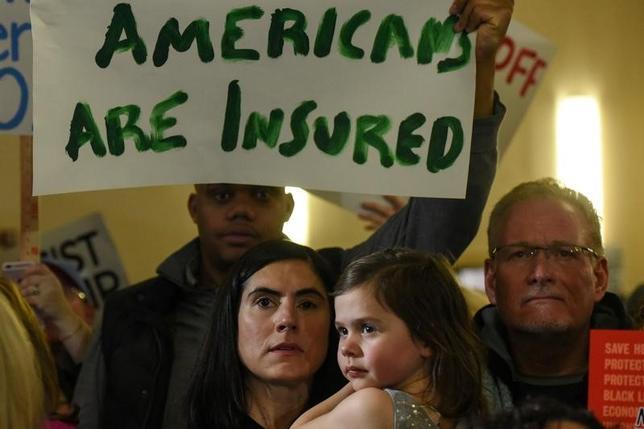 1月15日、トランプ次期米大統領は、米紙ワシントン・ポストのインタビューで、医療保険制度改革法(オバマケア)に代わる、「全ての人にとっての保険」制度の導入を目指すと述べた。写真はニュージャージー州ニューアークでオバマケア撤廃に動いているトランプ氏への異議を唱える人々(2017年 ロイター/Stephanie Keith)