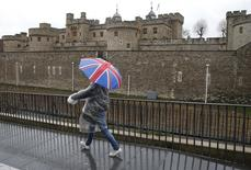 La primera ministra británica Theresa May estableció los principios que guiarán su estrategia para la salida de Reino Unido de la Unión Europea y definió 12 objetivos de negociación. En la imagen, un turista con un paraguas con la bandera británica camina junto a la Torre de Londres, el 15 de enero de 2017.  REUTERS/Peter Nicholls