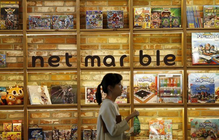 An employee walks past the logo of Netmarble Games at its headquarters in Seoul, South Korea, March 25, 2016. REUTERS/Kim Hong-Ji