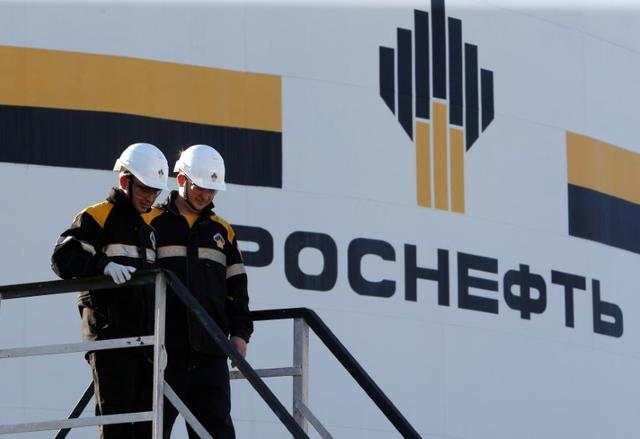 Workers stand next to a logo of Russia's Rosneft oil company at the central processing facility of the Rosneft-owned Priobskoye oil field outside the West Siberian city of Nefteyugansk, Russia, August 4, 2016. REUTERS/Sergei Karpukhin
