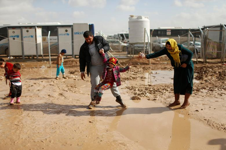 A displaced Iraqi family, who fled from Islamic State militants in Mosul, walk in the mud after heavy rain at Khazer camp, Iraq January 29, 2017. REUTERS/Ahmed Jadallah