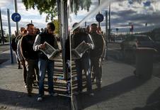 La economía española mantuvo en el periodo octubre-diciembre un fuerte ritmo de crecimiento que le permitió alcanzar una de las mayores tasas de crecimiento de la eurozona, pero la recuperación podría ralentizarse en los próximos meses ante un aumento de la inflación en el mercado nacional y mayores tensiones políticas a nivel mundial. En la imagen, un grupo de personas esperan en la fila del paro en Madrid el 4 de noviembre de 2014.    REUTERS/Andrea Comas/File Photo