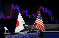 Флаги Японии и США в офисе трейдинговой компании в Токио 23 января 2017.    Японские политики дали отпор президенту США Дональду Трампу, обвинившему Токио в валютных манипуляциях, сказав, что страна придерживается договорённостей стран G20 о недопустимости девальвации валюты для получения конкурентного преимущества. REUTERS/Toru Hanai