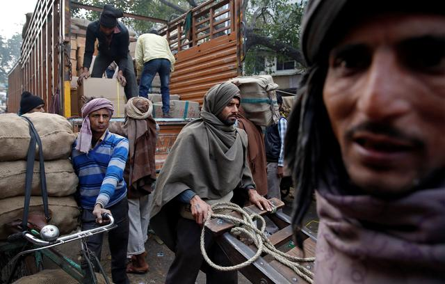 Porters move goods in the Chandni Chowk area of Old Delhi, India February 1, 2017. REUTERS/Cathal McNaughton