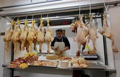 Un vendedor preparando unos pollos en un puesto en el mercado central de Lima, ago 29, 2014. Perú anotó una inflación de 0,24 por ciento en enero, por debajo de lo esperado por analistas, informó el miércoles el Instituto Nacional de Estadística e Informática (INEI).  REUTERS/Mariana Bazo