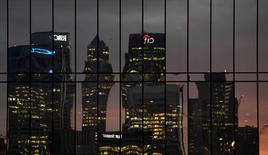 FILE PHOTO: The Canary Wharf business district is seen reflected in windows at dusk in London, Britain December 11, 2016. REUTERS/Toby Melville/File Photo