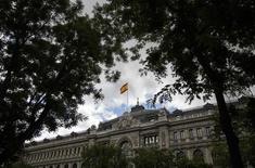 El Tesoro español colocó el jueves 4.315 millones de euros en cuatro referencias de deuda a medio y largo plazo, ligeramente por encima del objetivo fijado en unos 4.250 millones de euros y a unos tipos más altos que en la anterior subasta. En la imagen de archivo, una bandera española ondea sobre el edificio del Banco de España en Madrid,  REUTERS/Andrea Comas