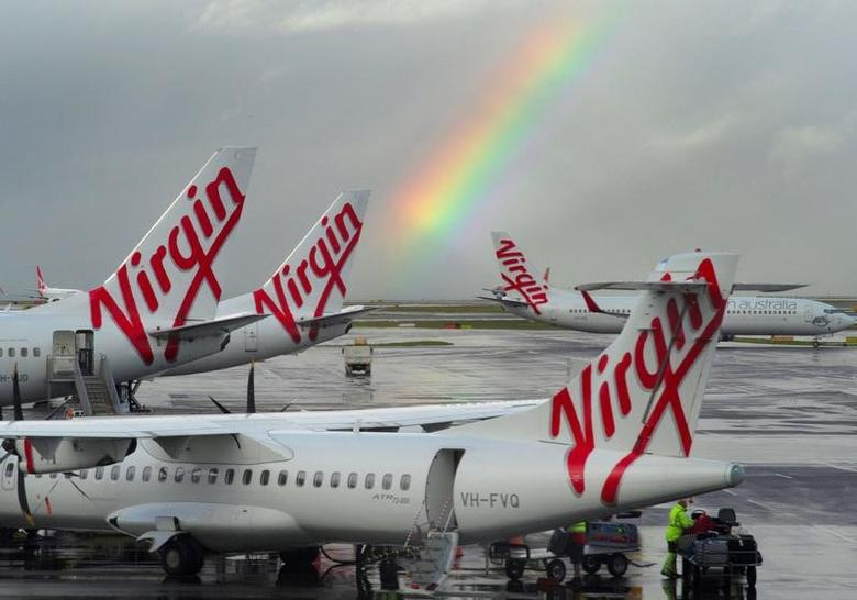 A rainbow from a passing rain shower sits over Virgin Australia aircraft at Sydney's Airport in Australia, August 5, 2016.  REUTERS/Jason Reed/File Photo