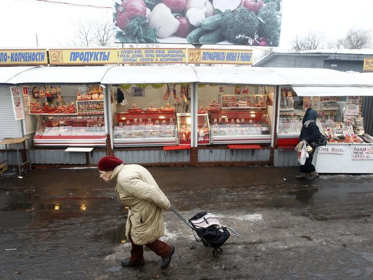 People walk past a market stall offering meat in Moscow February 8, 2013. REUTERS/Mikhail Voskresensky/Files