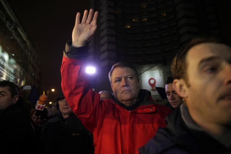 Romanian President Klaus Iohannis waves to protesters gathered at a demonstration against government plans to grant prison pardons and decriminalize some offences through emergency decree, in Bucharest, Romania, January 22, 2017. Inquam Photos/Liviu Florin Albei via REUTERS