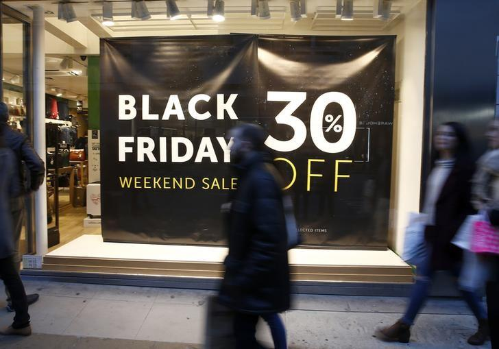 Shoppers walk past a store promoting ''Black Friday'' in London, Britain November 27, 2016.  REUTERS/Peter Nicholls/Files