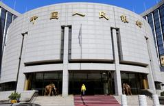 Imagen de archivo de una mujer caminando fuera de la sede del Banco Popular de China, en Pekín. 20 de noviembre 2013. El banco central de China sorprendió el viernes a los mercados financieros al elevar las tasas de interés de corto plazo en su primer día de operaciones después de un largo feriado, en una nueva señal de que su política está adoptando un sesgo más restrictivo a medida que la economía se estabiliza. REUTERS/Jason Lee/File Photo