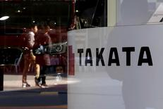 FILE PHOTO -  A logo of Takata Corp is seen with its display as people are reflected in a window at a showroom for vehicles in Tokyo, November 6, 2015. REUTERS/Toru Hanai/File Photo