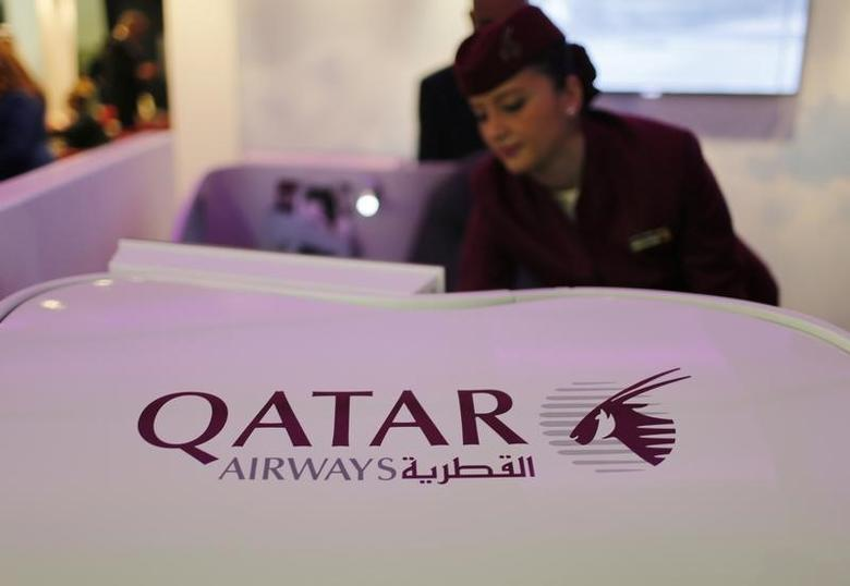A Qatar Airways flight stewardess shows the airline's new business class seat during the Arabian Travel Market exhibition in Dubai May 6, 2013. Qatar Airways had to forego $200 million in lost revenue up until April 2013 because of the grounding of Boeing's 787 planes, the airline's Chief Executive Akbar Al Baker said on Monday. REUTERS/Ahmed Jadallah (UNITED ARAB EMIRATES - Tags: TRANSPORT BUSINESS) - RTXZCC3