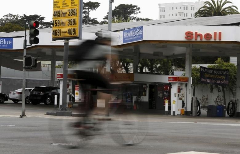 A cyclist rides past a sign showing the prices of gas at a filling station in San Francisco, California July 22, 2015.    REUTERS/Robert Galbraith