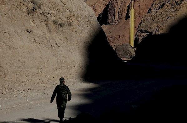 2月4日、イラン革命防衛隊の空軍部門司令官は、同国の安全保障が脅威にさらされた場合、保有するミサイルを使用すると明言し、弾道ミサイル実験を受けて米国が課した新たな制裁に対抗する姿勢を示した。写真は弾道ミサイル発射実験が行われる中を歩く兵士。イラン国内(場所不明)で撮影。昨年3月イランの通信社FARSNEWS提供(2017年 ロイター)