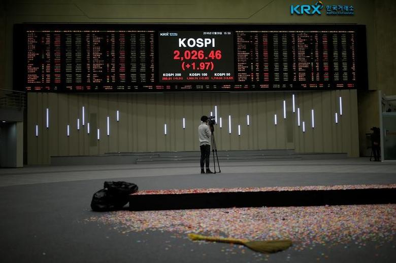 A journalist films the final stock price index after the ceremonial closing event of the 2016 stock market in Seoul, South Korea, December 29, 2016.  REUTERS/Kim Hong-Ji