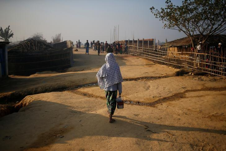 A Rohingya refugee walks on with a tiffin carrier in the morning at Kutupalang Unregistered Refugee Camp, in Cox's Bazar, Bangladesh, February 4, 2017. REUTERS/Mohammad Ponir Hossain.