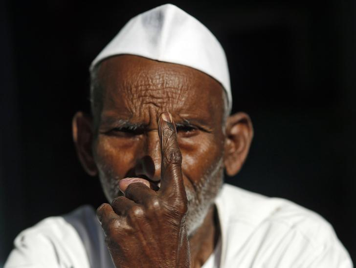 FILE PHOTO: A man shows his ink-marked finger after casting his vote outside a polling station in Parla village in Muzaffarnagar district in Uttar Pradesh April 10, 2014. REUTERS/Anindito Mukherjee/Files
