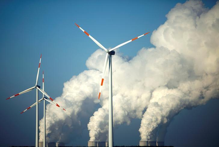 FILE PHOTO - Steam billows from the cooling towers of Vattenfall's Jaenschwalde brown coal power station behind wind turbines near Cottbus, Germany, December 2, 2009.    REUTERS/Pawel Kopczynski/File Photo