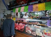 Una persona realizando compras en una carnicería en Buenos Aires, jul 31, 2014. Los precios minoristas de Argentina habrían avanzado en promedio un 1,7 por ciento en enero, liderados por incrementos en combustibles y alimentos, según un sondeo de Reuters publicado el martes.  REUTERS/Enrique Marcarian/File Photo