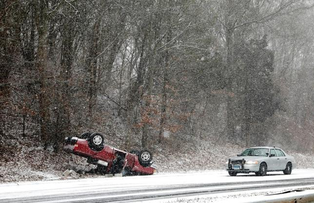 A Connecticut State Police vehicle stands by a flipped over car in falling snow after an accident on the Merritt Parkway South in Hamden, Connecticut, U.S., January 31, 2017. REUTERS/Mike Segar