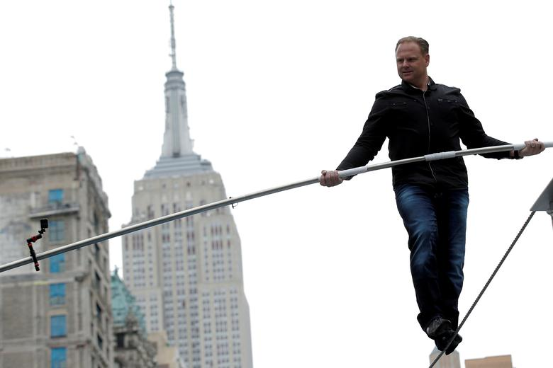 File Photo: Aerialist Nik Wallenda walks a tightrope during a promotional event in midtown Manhattan, with the Empire State Building behind him, in New York City, U.S., May 17, 2016.  REUTERS/Brendan McDermid