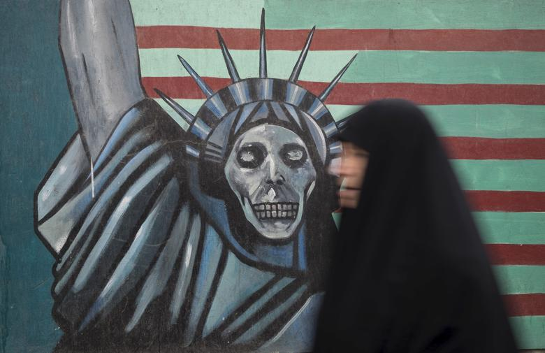 An Iranian woman walks past an anti-U.S. mural painted on the wall of the former U.S. Embassy in Tehran November 4, 2015. REUTERS/Raheb Homavandi