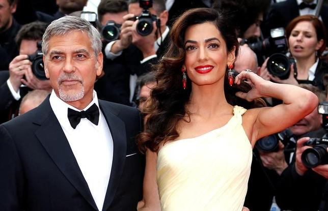 Cast member George Clooney and his wife Amal pose on the red carpet as they arrive during the 69th Cannes Film Festival in Cannes, France on May 12, 2016.  REUTERS/Eric Gaillard/File Photo