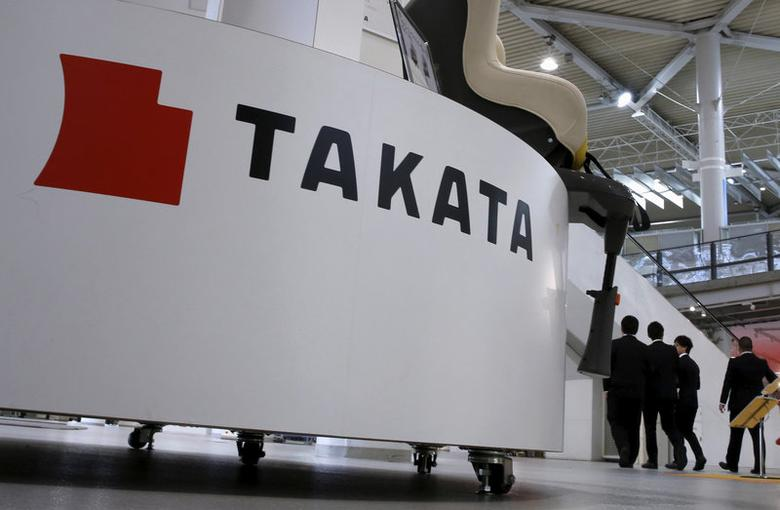 FILE PHOTO: Visitors walk behind a logo of Takata Corp on its display at a showroom for vehicles in Tokyo, Japan, November 6, 2015. REUTERS/Toru Hanai/File Photo