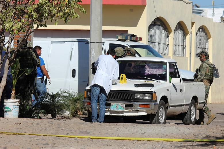 A forensic technician and Mexican marines work at a crime scene after a shooting with unknown assailants in Culiacan, Mexico, February 7, 2017. REUTERS/Jesus Bustamante