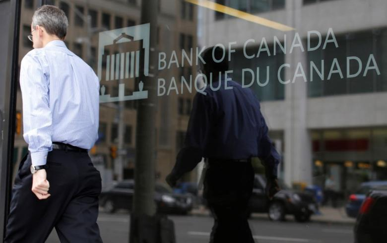 A man is reflected in a window while walking past the Bank of Canada office in Ottawa, Ontario, Canada, May 25, 2016. REUTERS/Chris Wattie