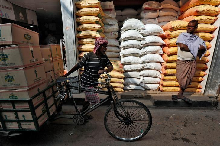 FILE PHOTO: A labourer carries vegetable oil packets on a tricycle as a man stands in front of his shop selling food grains, at a wholesale market in Kolkata, India, January 4, 2017. REUTERS/Rupak De Chowdhuri/File photo