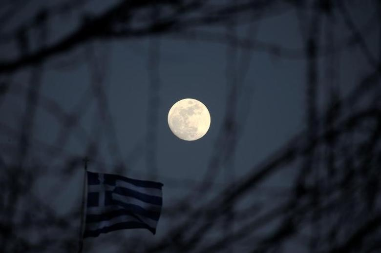 The moon rises next to a fluttering Greek national flag in Athens, Greece February 9, 2017. REUTERS/Alkis Konstantinidis - RTX30BVX