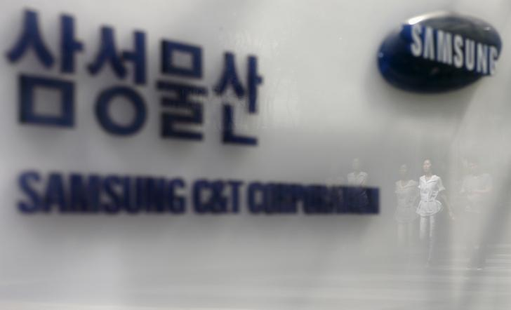 Employees are reflected on a logo of Samsung C&T Corp at the company's headquarters in Seoul, South Korea, July 16, 2015. REUTERS/Kim Hong-Ji/File Photo